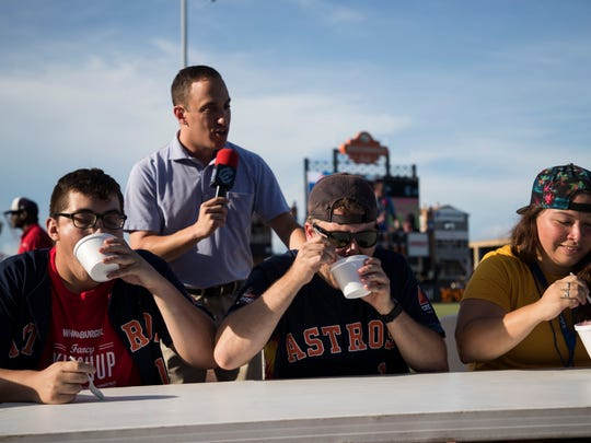 Ryan Garza (from left), Joe Day, and Julie Garcia, compete in a raspas easting contest on Saturday, July 7, 2018, at Whataburger Field.