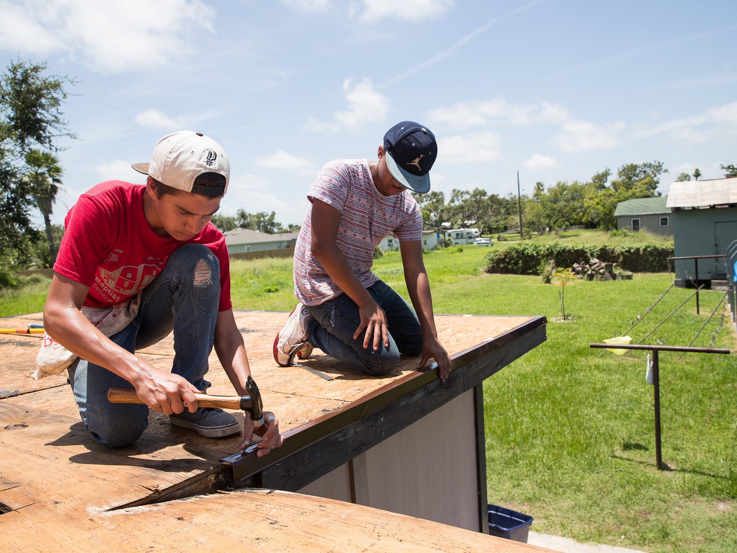 Joshua Hauser and Jacob Peeler, volunteering with the Bounce recovery project, help replace a roof damaged by Hurricane Harvey on a home in Rockport on Wednesday, July 18, 2018.