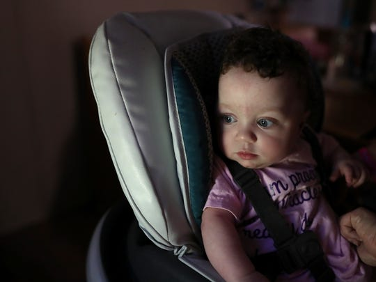 Lilly June, 11 months, is strapped into her feeding chair at the family home on Thursday, July 12, 2018. Though she is predominantly fed formula through a gastrostomy tube that is surgically implanted in her stomach, her nurses and family feed her semi-regularly in hopes that the tube can eventually be removed.