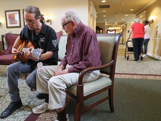Patrick Nettesheim (left) helps tune the guitar before David McMahon plays it.