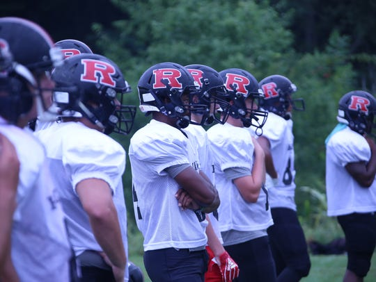 Rossview players watch while teammates go through drills during the first day of full pads Monday.