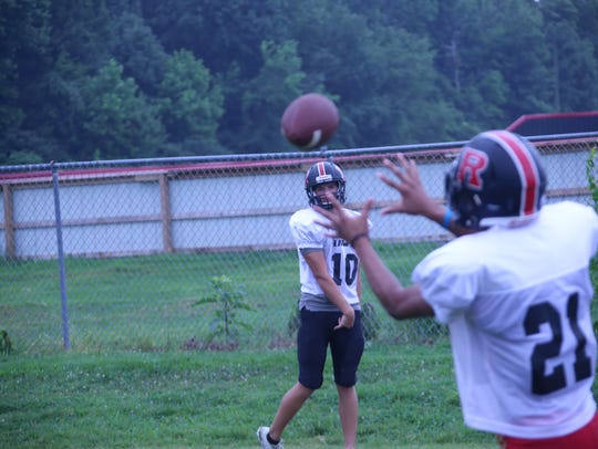 Rossview quarterback Nick Harbor (10) warms up with a teammate during practice Monday.