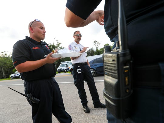 "Paramedic/field training officer Brian Garcia, left, and Lt. Jonathan Henderson, right, talk with their co-workers. ""I don't eat tacos,"" said Henderson, who lost 56 pounds after running ambulances for years and finding himself out-of-shape. ""I'm now the vegan who packs my own food."""