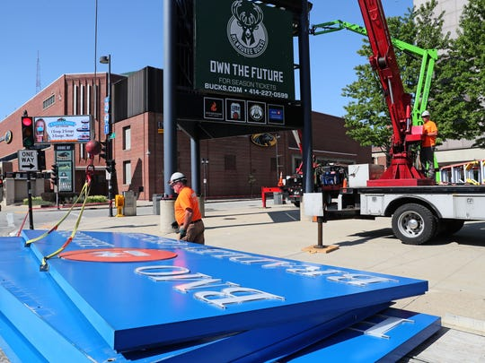 July 25, 2018 A crew from Lemberg Sign and Lighting, takes down signage from in front of the BMO Harris Bradley Center. Here Mike Barutha (left) gets the sign loaded onto a trailer.  Corey Herman (right) operates the crane that lowered the signs.