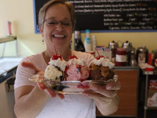 Andrea Holliday, owner of the Independent Ice Cream Shop, holds the shop's first banana split.