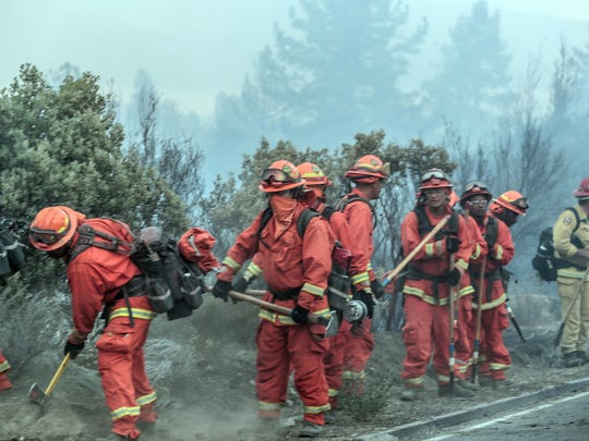 A group of convict fire fighters prepare to deploy