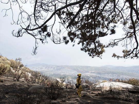 A firefighter prepares to leave where homes were destroyed by the Cranston Fire on Sunday July 29, 2018.
