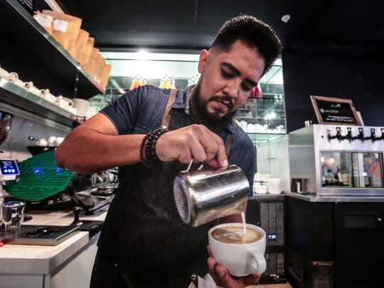 Barista Steve Garcia pours a pattern on a latte at