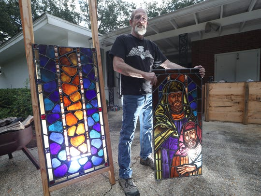 Bill Dodds, a stained glass master craftsman, stands