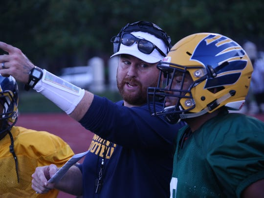 Northeast High coach Chad Watson talks with quarterback Heath Williams after an offensive possession against Pearl Cohn Friday in a scrimmage.