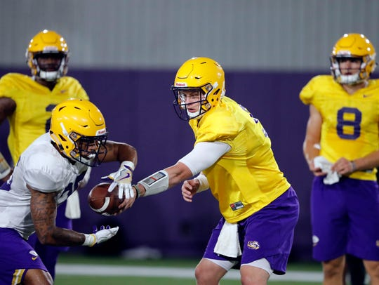 LSU quarterback Joe Burrow hands off to LSU running