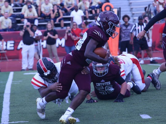 A West Creek running back tries to escape the tackle