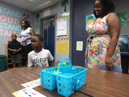 Josemane Ancion welcomes Peter Erhiawarie, 5, to her kindergarten class on the first day of school at Pineview Elementary on Monday, Aug. 13, 2018.
