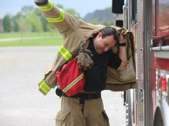 Firefighter Zach Morris demonstrates the process of dressing for an active fire call as he waits for a call at Rutherford County Fire Rescue Department Station 1 on Barfield Road on Aug. 16, 2018.