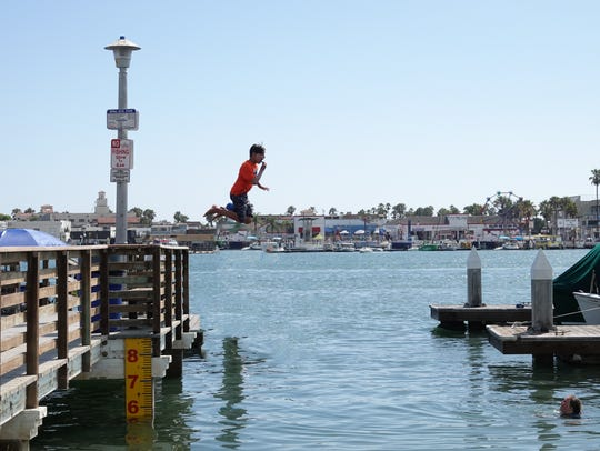 Jumping off a dock into the waters of lower Newport