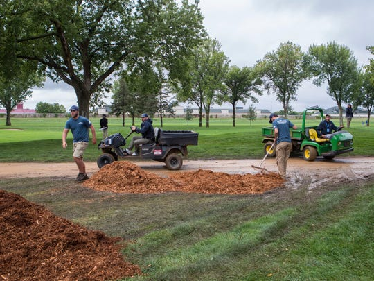 Weller Brothers Landscaping workers add mulch to the