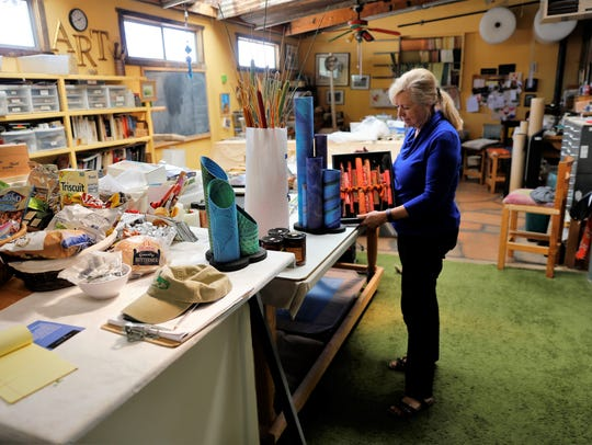 Artist Bev Taylor looks over some of her work in her