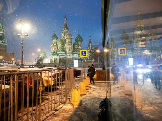 A man walks as it snows, with the Spasskaya Tower,