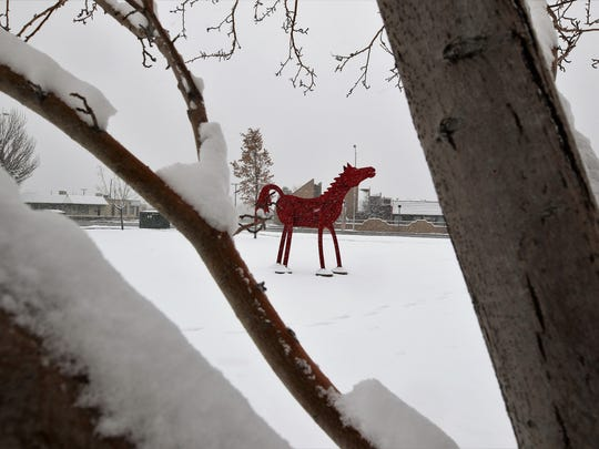A horse sculpture on the south lawn of the Farmington Public Library is framed by the snow-covered branches of a tree Tuesday.