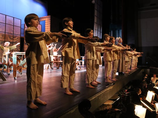 "Several young actors line the front of the stage during a Monday rehearsal for the San Juan College production of ""Oliver!"""