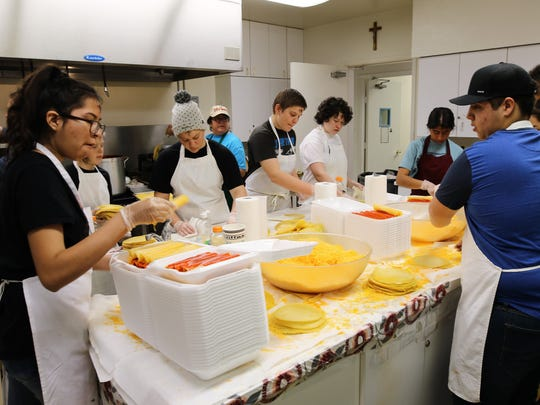 Members of the St. Mary's Youth Group prepare orders Wednesday during the 20th annual Cheese Enchilada Take-Out fundraiser in the kitchen of the St. Mary's Parish Center in Farmington.