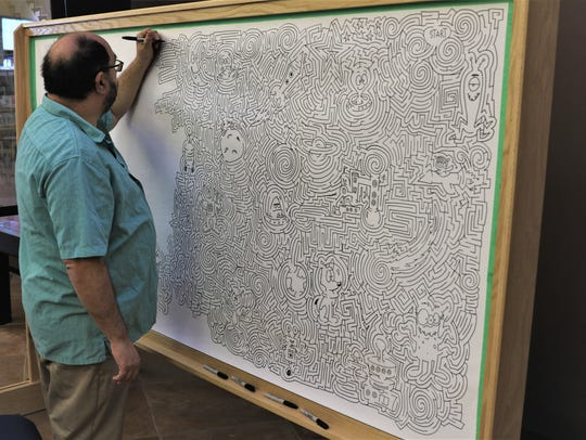 Artist Joe Wos continues working on a maze mural Tuesday