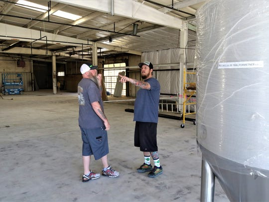 Brandon Beard, right, owner and brew master at the Lauter Haus Brewing Company, discusses a detail of the operation with one of his partners, Brad Foley, on Friday.