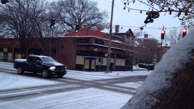 Snowy driving conditions at First and Oak Streets in Old Louisville on Tuesday morning, December 10, 2013.