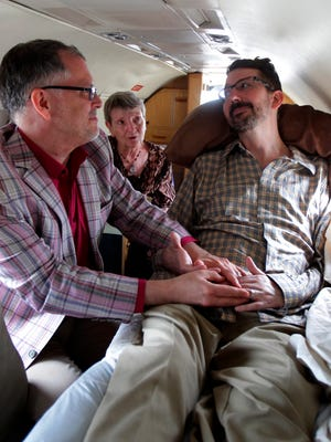 In this July 11, 2013, photo, Jim Obergefell, left and John Arthur, right, are married by officiant Paulette Roberts, rear center, in a plane on the tarmac at Baltimore/Washington International Airport in Glen Burnie, Md. Arthur died in October from Lou Gerhig's disease.