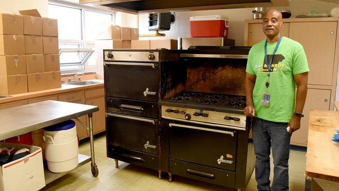 """Manuel Hoskins, director of the Opportunity Center at ALCC, stands by the facility's antique stove/oven. The center's kitchen is being relocated from its current upper floor location to a larger footprint downstairs near the community room. """"This old stove was here when I was a kid,"""" Hoskins said."""