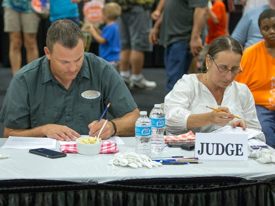 Indy Star food and dining reporter Liz Biro,  far right, take her role seriously, smelling, eyeballing, conferring with other judges and jotting notes for each of the in the American Dairy Association Indiana Ultimate Macaroni and Cheese Recipe Contest at the 2015 Indiana State Fair.