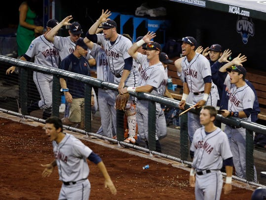 Players in the Virginia dugout celebrate after Virginia's Brandon Downes hit an RBI triple in the sixth inning of Game 2 of the best-of-three NCAA baseball College World Series finals against Vanderbilt in Omaha, Neb., Tuesday, June 24, 2014. (AP Photo/Nati Harnik)