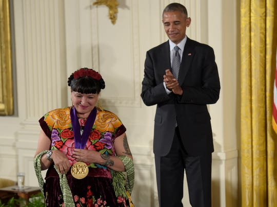 President Barack Obama applauds author Sandra Cisneros after presenting her with the 2015 National Medal of Arts during a ceremony in the East Room of the White House in Washington, Thursday, Sept. 22, 2016.