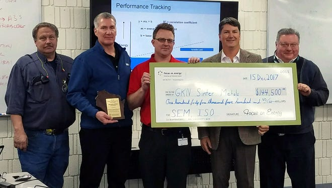 GKN Sinter Metals employees  John Martin, Wayne Spearman, John Rau, Richard Feustel and We Energies principal Account manager Roger M. Kirgues on Dec. 15 hold a check for $144,500 from Focus on Energy, an energy efficiency and renewable energy program funded by participating electric and natural gas utilities.