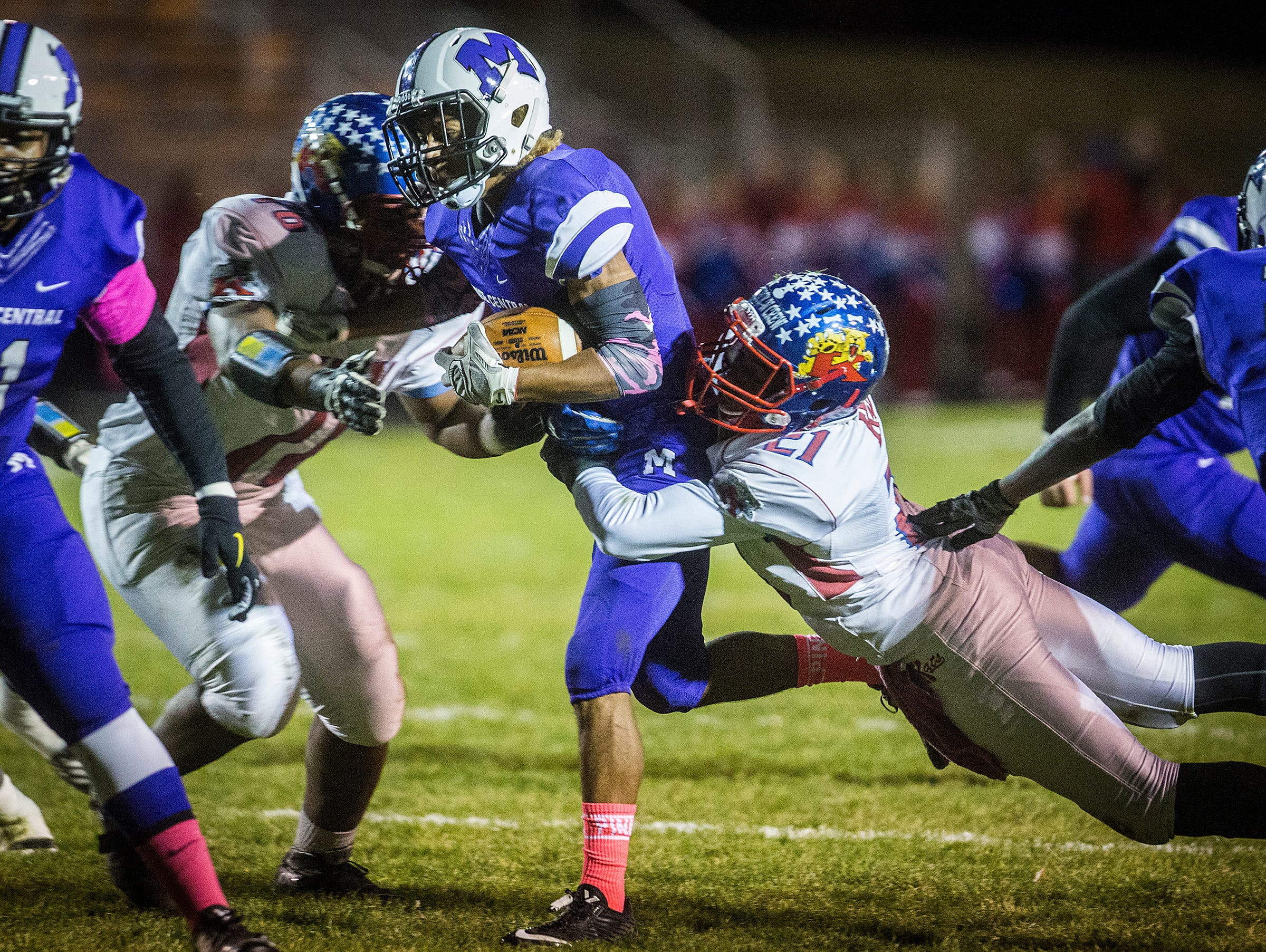 Central's Exuse Brown fights past Kokomo's defense during their game at Central Friday, Oct. 30, 2015.