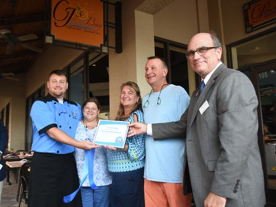 David Longfield-Smith of Blue Zones SW Florida, right, and CJ's executive team display their Blue Zones certificate. CJ's on the Bay was recognized Tuesday afternoon as the first organization on Marco Island to be awarded Blue Zones certification.