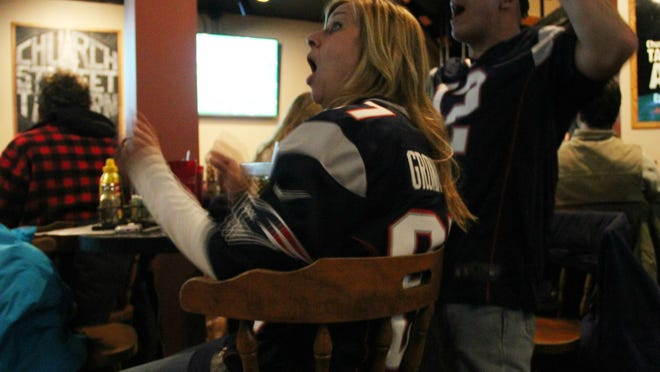 Caryn Duncan, left, and Jeff Koss of Portsmouth, N.H. cheer at the Church Street Tavern in Burlington as the New England Patriots score a touchdown during Super Bowl XLIX on Sunday.