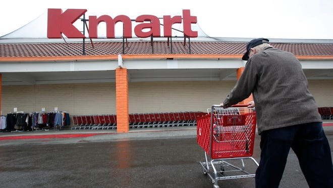A customer pushes a shopping cart outside a Kmart store in Redwood City, Calif.