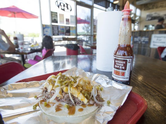 A Texas Taco is served with pulled pork, cheese potatoes and sauce at Serious Texas Bar-B-Q.