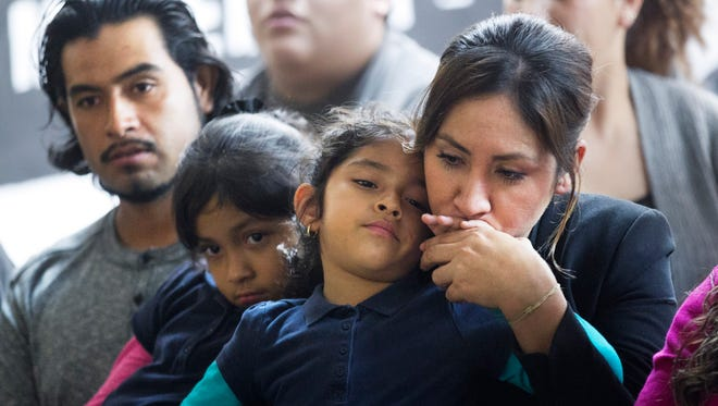 Ana Patino (right) of Phoenix, who is an undocumented immigrant kisses the hand of her daughter, Natalie Cruz, 5, who is a U.S. citizen as Ana's husband and the girl's father, Rafael Cruz, (left) who is also undocumented sits with Camila Cruz, a U.S. citizen, during a watch party for President Obama's speech on executive action for deferred action for undocumented immigrants, at the Puente offices in Phoenix on Thursday, November 20, 2014.