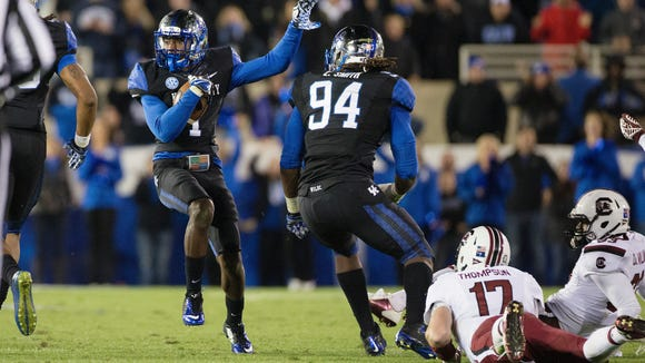 Kentucky wide receiver A J. Stamps dodges South Carolina players after he intercepted a pass by South Carolina quarterback Dylan Thompson, right, to set up a key field goal late in the first half.