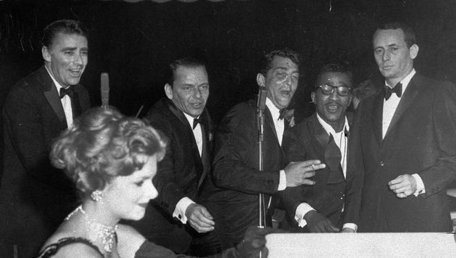 """Members of the """"Rat Pack,"""" from left, Peter Lawford, Frank Sinatra, Dean Martin, Sammy Davis Jr., and Joey Bishop, perform at the Sands Hotel in Las Vegas Jan. 20, 1960. Woman at left is unidentified. (AP Photo)"""