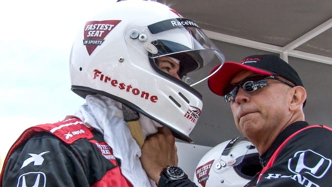 Indy Racing Experience co-owner Scott Jasek (right) helps get IndyStar Motor Sports Insider Jim Ayello ready for his two-seater ride with Mario Andretti on Saturday at Indianapolis Motor Speedway.