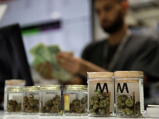 A cashier rings up a marijuana sale at the Essence