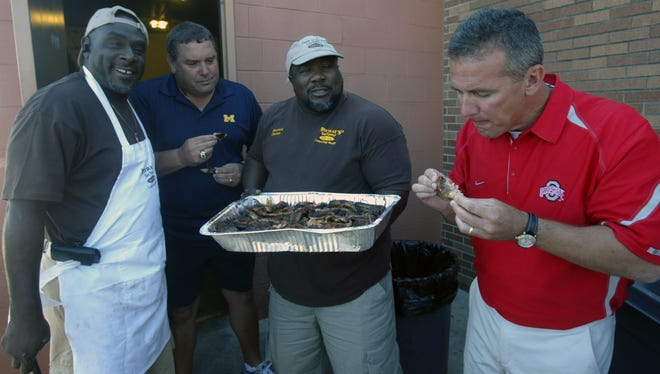 Michigan football coach Brady Hoke, left, and Ohio State coach Urban Meyer, right, enjoy a rib during the Sound Mind Sound Body football camp June 13, 2012, at Southfield High.