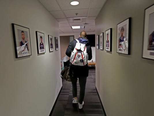 In this Sunday, Jan. 28, 2018 photo, Washington head coach Mike Hopkins wears his USA Basketball backpack as he walks past photos of current Washington players in the hallway leading to his office before an NCAA college basketball game against Washington State in Seattle. Hopkins has served as an assistant coach for Team USA during several championship seasons, and one of the most surprising stories in college basketball is what Hopkins is doing in his first season at Washington and how the Huskies are in the conversation for an NCAA bid entering February. (AP Photo/Ted S. Warren)