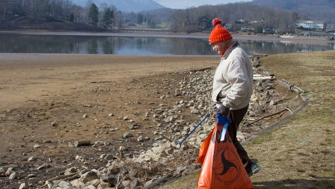 A worker cleans up litter during the recent drawdown of Lake Junaluska in Haywood County.