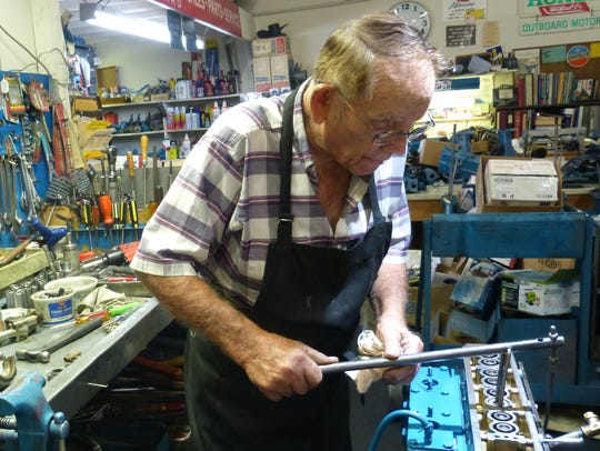 Ed Ewing of Redding works on an outboard motor Friday