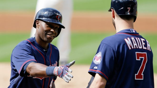 Minnesota Twins' Torii Hunter, left, is congratulated by Joe Mauer after Hunter hit a solo home run against the Cleveland Indians on May 9, 2015. The Twins have become a surprise contender early in the AL Central.