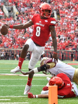 Louisville Cardinals quarterback Lamar Jackson (8) avoids the tackle of Florida State Seminoles linebacker Dontavious Jackson (5) during the second quarter at Papa John's Cardinal Stadium.